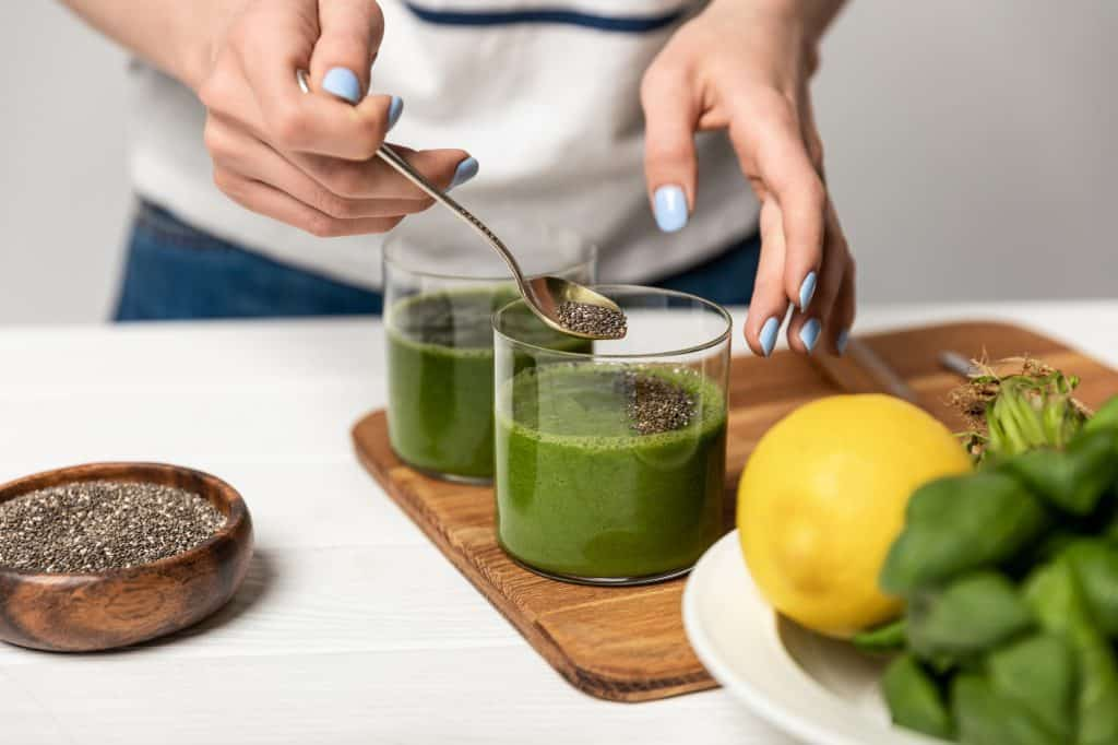 Woman putting chia seeds into a drink of fresh juice