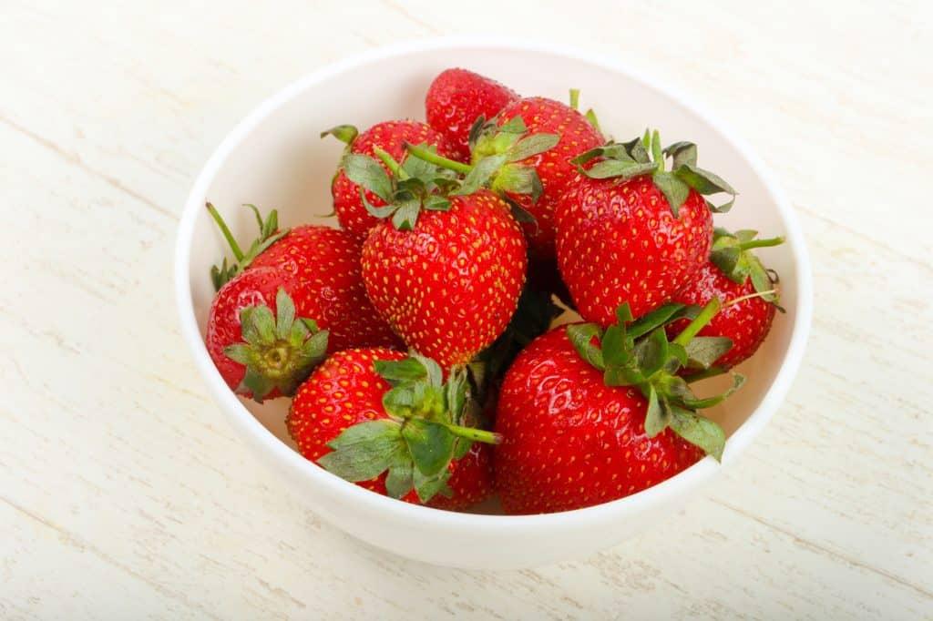 fresh strawberries in a white bowl