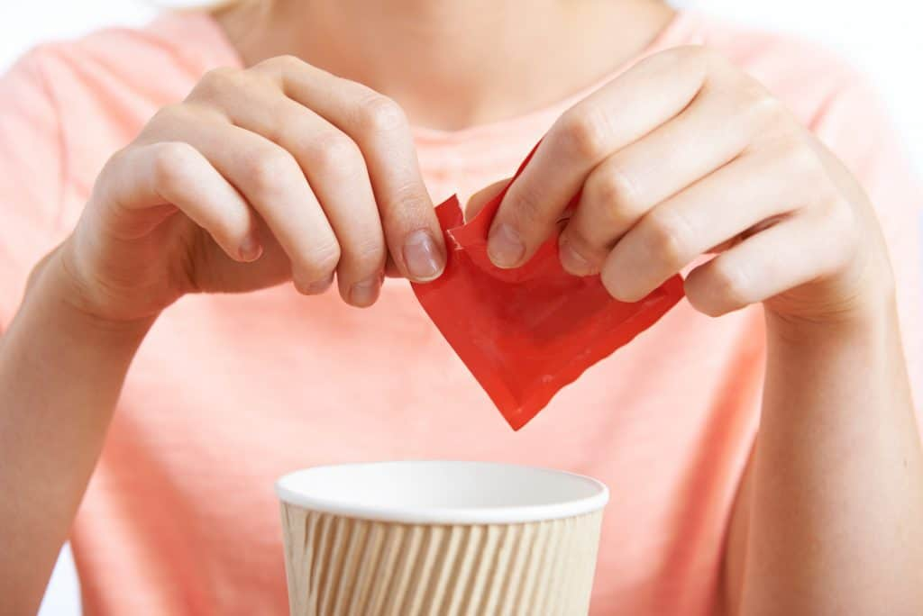 woman adding artificial sweetener to a drink