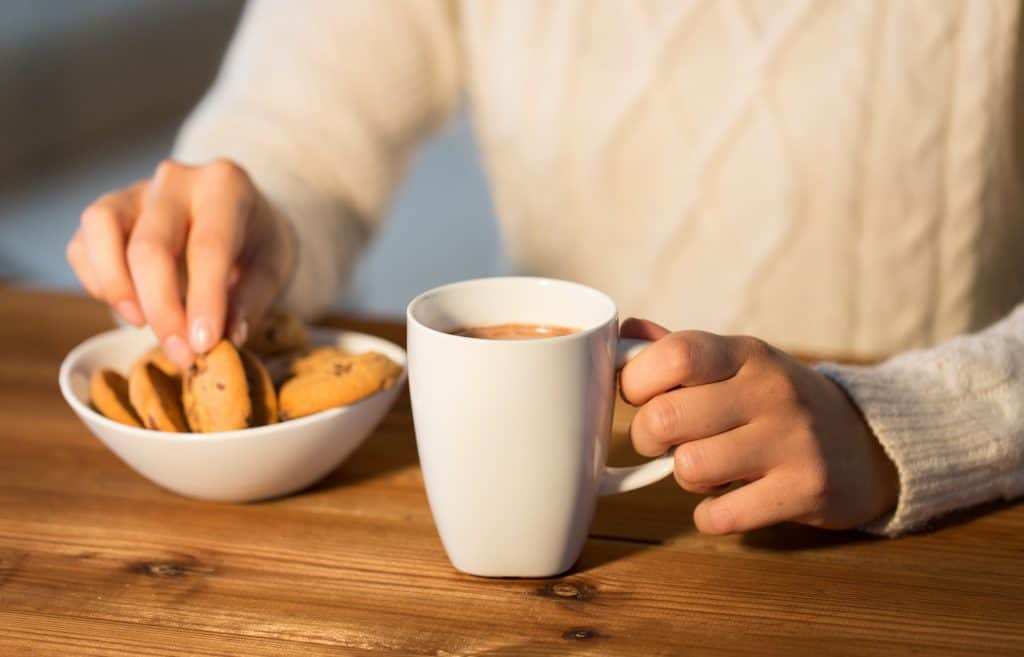 woman with lactation cookies and hot chocolate cup