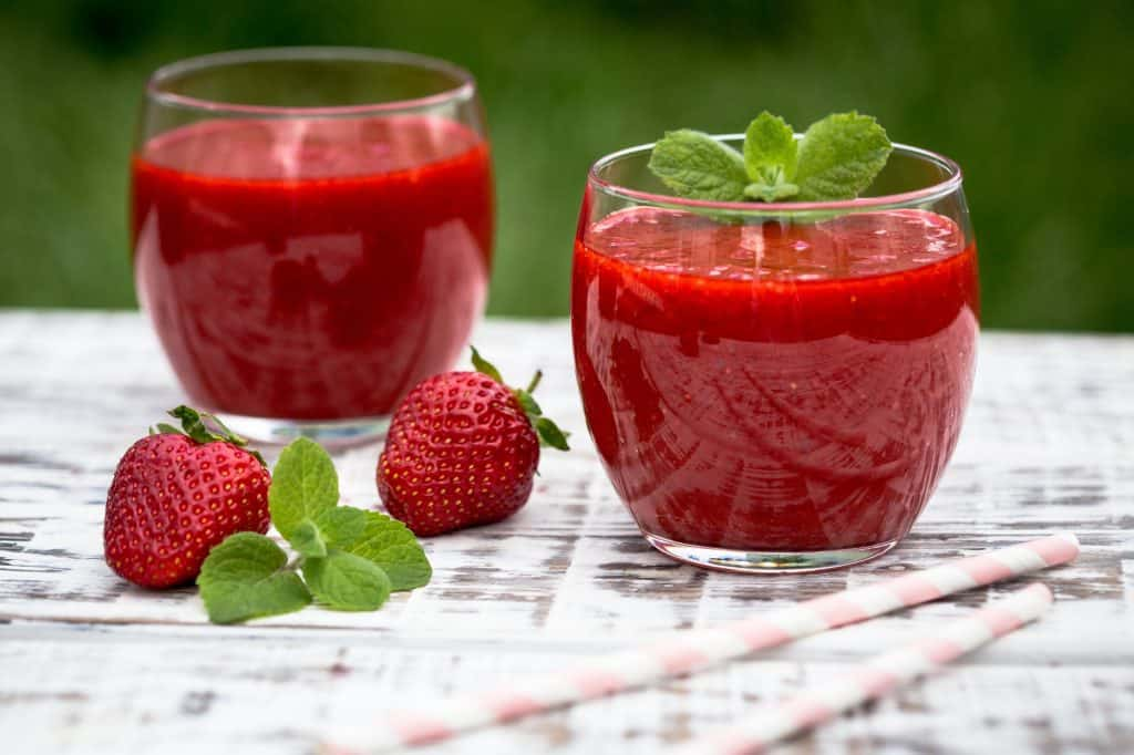 two glasses of strawberry juice with fresh strawberries and mint