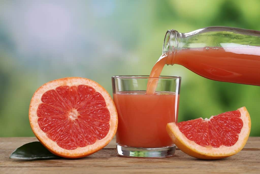 Fresh red grapefruit juice being poured into a glass