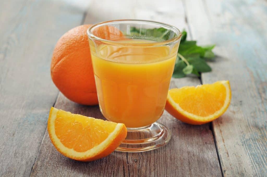 orange juice with fresh orange fruit on a wooden table